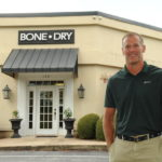 Chad Collins posing in front of Bone Dry Roofing Company office.